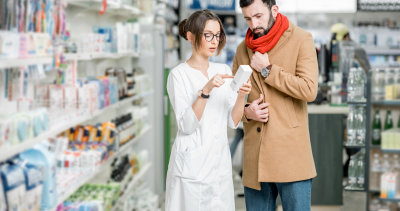 pharmacist choosing medicine with male client in the pharmacy store