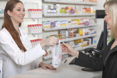 female pharmacist hands over a plastic sachet with medicine